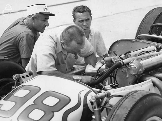 Owner J.C. Agajanian and driver Troy Ruttman look on as mechanic