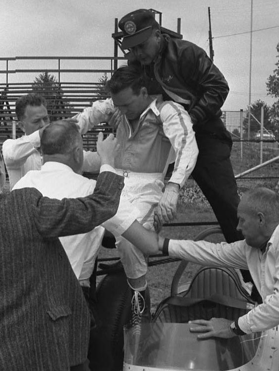 Jacobi being lifted out of his car, 1963. Note the use of neck brace, body board, etc. not. (Johnson)