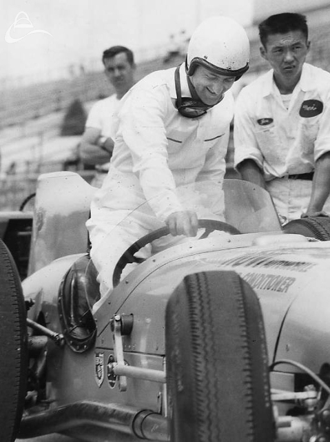 Eddie Sachs climbs out of his Novi, grinning like a cheshire cat. 1958. (UPI/Smith)