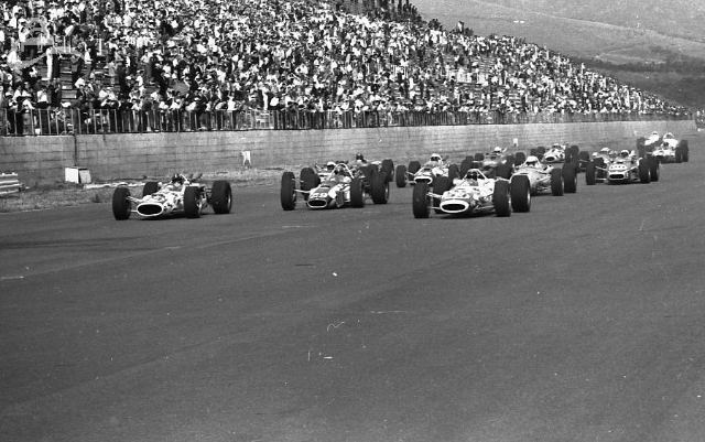 Fuji, 1966. Graham Hill (24) and Jackie Stewart (43) flank Lloyd Ruby (29) at the start. (Johnson)
